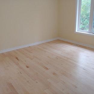 Foto di una camera degli ospiti design di medie dimensioni con pareti beige, parquet chiaro e pavimento giallo