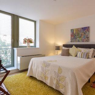 Immagine di una camera matrimoniale design con pareti bianche e pavimento in compensato