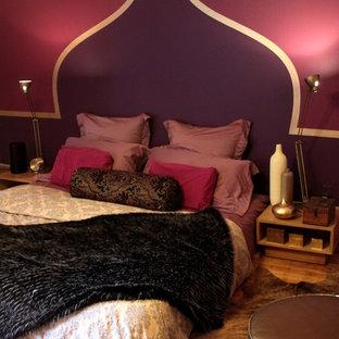 Foto di una camera matrimoniale eclettica di medie dimensioni con pareti viola e pavimento in legno massello medio