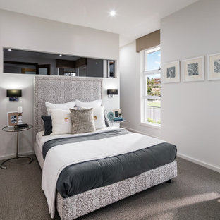 This is an example of a mid-sized contemporary master bedroom in Newcastle - Maitland with white walls, carpet and grey floor.