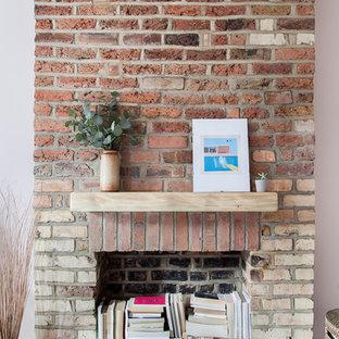 Стильный дизайн: хозяйская спальня среднего размера в стиле фьюжн с розовыми стенами, деревянным полом, стандартным камином, фасадом камина из кирпича и белым полом - последний тренд