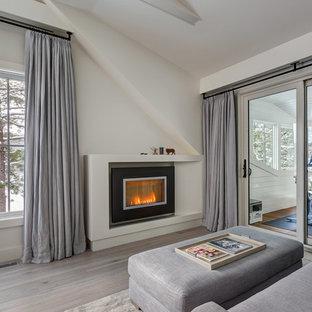 На фото: хозяйская спальня среднего размера в современном стиле с белыми стенами, светлым паркетным полом, горизонтальным камином, фасадом камина из штукатурки и серым полом с
