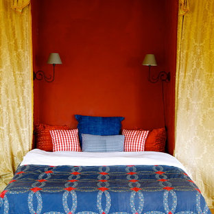 This is an example of a mid-sized mediterranean guest bedroom in New York with red walls and medium hardwood floors.