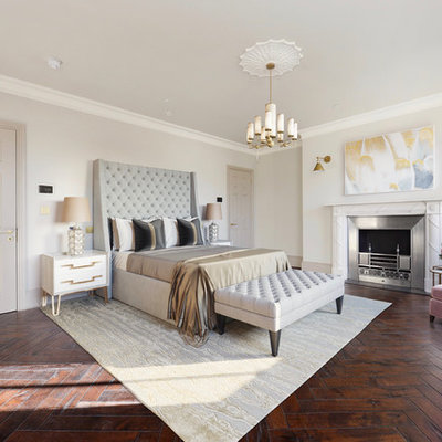 Example of a trendy master dark wood floor bedroom design in London with beige walls, a standard fireplace and a metal fireplace