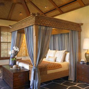 Imagen de dormitorio exótico con paredes blancas y suelo de pizarra
