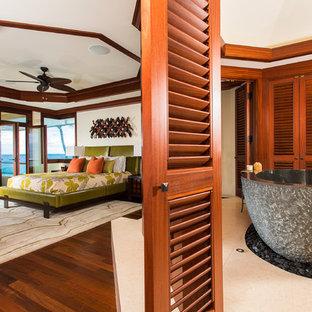 Bild på ett stort tropiskt huvudsovrum, med beige väggar och mörkt trägolv