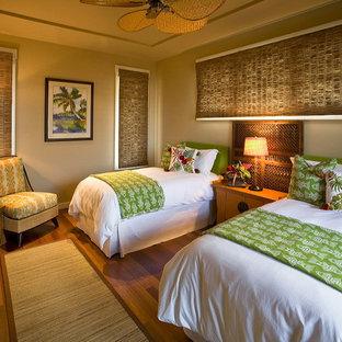 Foto på ett tropiskt gästrum, med grå väggar och mörkt trägolv