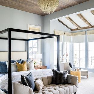 На фото: класса люкс большие хозяйские спальни в стиле современная классика с синими стенами, ковровым покрытием, стандартным камином и фасадом камина из камня