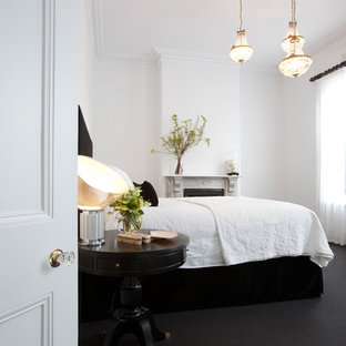 Photo of a contemporary bedroom in Melbourne with white walls, carpet, a standard fireplace and black floors.