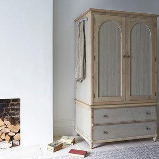 Ejemplo de dormitorio principal, campestre, grande, con paredes blancas, suelo de madera pintada, chimenea tradicional y marco de chimenea de yeso