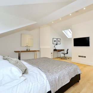 This is an example of a medium sized contemporary master bedroom in London with white walls, light hardwood flooring and beige floors.