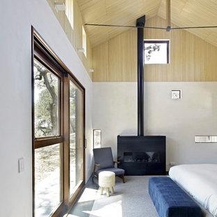 Foto de dormitorio principal, rústico, grande, con paredes blancas, suelo de cemento, estufa de leña, marco de chimenea de metal y suelo gris