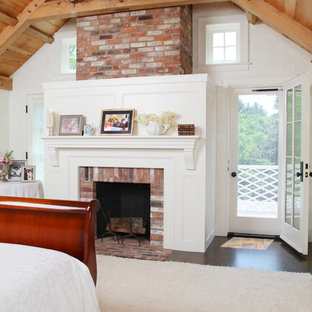 This is an example of a large country master bedroom in Boston with white walls, dark hardwood floors, a standard fireplace, a brick fireplace surround and brown floor.