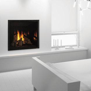 Esempio di una piccola camera degli ospiti minimalista con pareti bianche, pavimento in legno verniciato, camino classico, cornice del camino in intonaco e pavimento bianco