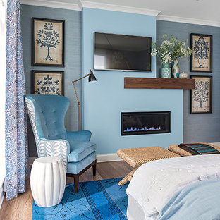 This is an example of a mid-sized contemporary master bedroom in Minneapolis with blue walls, a ribbon fireplace, light hardwood floors, a metal fireplace surround and blue floor.
