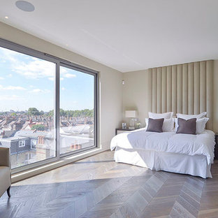 Large trendy master medium tone wood floor bedroom photo in London with white walls and no fireplace