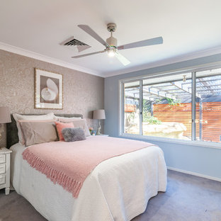 Transitional bedroom in Sydney with blue walls, carpet and beige floor.