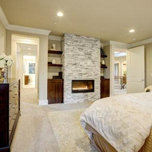 Idées déco pour une chambre craftsman de taille moyenne avec un mur beige, une cheminée standard, un manteau de cheminée en pierre de parement et un sol beige.
