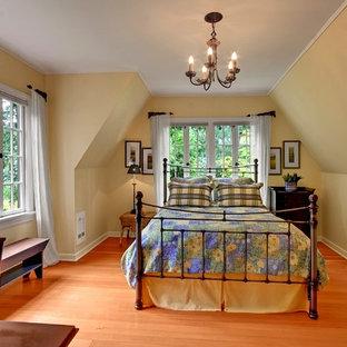 Mittelgroßes Landhausstil Schlafzimmer mit braunem Holzboden, gelber Wandfarbe und orangem Boden in Seattle
