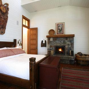 Imagen de dormitorio rústico con marco de chimenea de piedra y chimenea tradicional