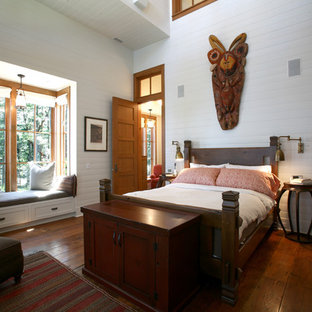Example of a mountain style medium tone wood floor bedroom design in Seattle with white walls and no fireplace