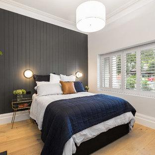 メルボルンの中サイズのコンテンポラリースタイルのおしゃれな主寝室 (グレーの壁、淡色無垢フローリング、標準型暖炉、金属の暖炉まわり) のインテリア