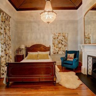 Imagen de habitación de invitados tradicional, pequeña, con paredes grises, chimenea tradicional, marco de chimenea de yeso, suelo marrón y suelo de madera en tonos medios
