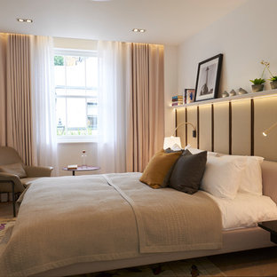 Design ideas for a contemporary bedroom in London with white walls, light hardwood flooring and no fireplace.