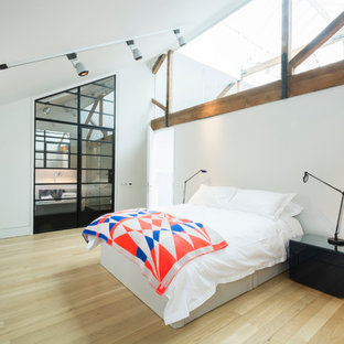 Inspiration for an expansive industrial loft-style bedroom in London with white walls and light hardwood floors.
