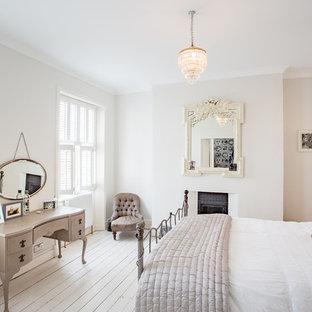 Immagine di una camera da letto chic di medie dimensioni con pareti grigie, pavimento in legno verniciato, camino classico, cornice del camino in intonaco e pavimento bianco