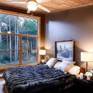 Inspiration pour une chambre parentale chalet de taille moyenne avec un sol en bambou, aucune cheminée, un sol marron et un mur gris.