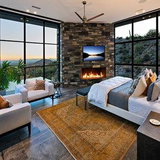 Imagen de dormitorio principal, actual, grande, con suelo de baldosas de porcelana, chimenea lineal y marco de chimenea de piedra