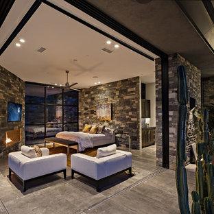 Diseño de dormitorio principal, actual, extra grande, con paredes multicolor, suelo de baldosas de porcelana, chimenea tradicional, marco de chimenea de piedra y suelo gris