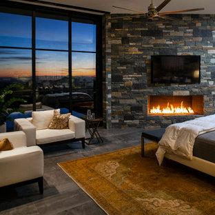 Modelo de dormitorio principal, actual, extra grande, con paredes blancas, suelo de baldosas de porcelana, chimenea tradicional, marco de chimenea de piedra y suelo gris