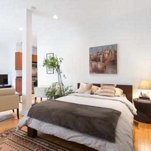 Foto på ett vintage sovrum, med vita väggar, mellanmörkt trägolv och orange golv