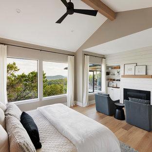 オースティンの中サイズのトランジショナルスタイルのおしゃれな主寝室 (グレーの壁、淡色無垢フローリング、標準型暖炉、木材の暖炉まわり、ベージュの床) のレイアウト