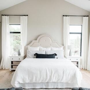 Idéer för stora lantliga huvudsovrum, med grå väggar, ljust trägolv, en standard öppen spis, en spiselkrans i sten och brunt golv
