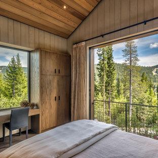 Cette image montre une chambre parentale chalet en bois de taille moyenne avec un mur beige, un sol en bois brun, aucune cheminée, un sol marron et un plafond en bois.
