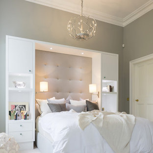 This is an example of a large transitional guest bedroom in London with grey walls, carpet and no fireplace.