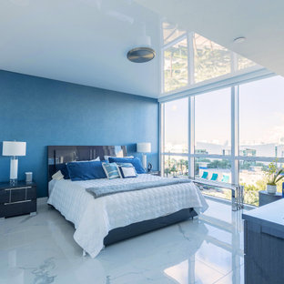 This is an example of a modern master bedroom in Miami with blue walls, porcelain floors, wallpaper and wallpaper.
