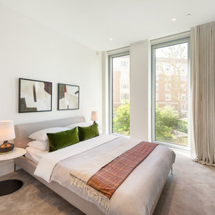 Medium sized contemporary bedroom in London with white walls, carpet, grey floors and no fireplace.