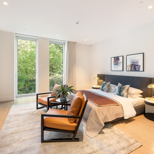 Medium sized contemporary master bedroom in London with white walls, beige floors, light hardwood flooring and no fireplace.