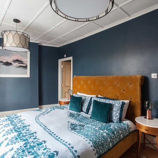 This is an example of an eclectic bedroom in London with blue walls, medium hardwood flooring and brown floors.