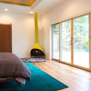 Design ideas for a large midcentury master bedroom in Boise with white walls, medium hardwood floors and a corner fireplace.