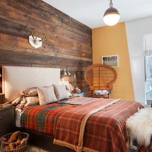 This is an example of a country guest bedroom in New York with orange walls and dark hardwood floors.