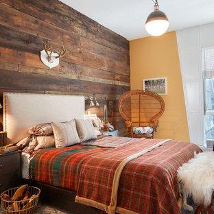 На фото: гостевая спальня в стиле рустика с оранжевыми стенами и темным паркетным полом с
