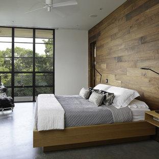 На фото: спальня в стиле модернизм с бетонным полом и серым полом с