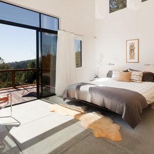 Идея дизайна: большая хозяйская спальня в современном стиле с белыми стенами, бетонным полом, стандартным камином, фасадом камина из бетона и серым полом