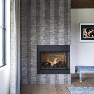 デンバーの中サイズのエクレクティックスタイルのおしゃれな主寝室 (白い壁、無垢フローリング、コーナー設置型暖炉、漆喰の暖炉まわり、ベージュの床) のレイアウト