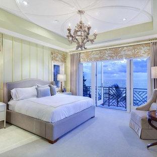 На фото: огромная хозяйская спальня в классическом стиле с зелеными стенами, ковровым покрытием и белым полом без камина